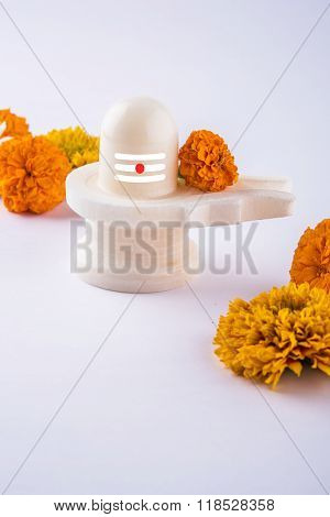 Shiva Linga made up of white marble decorated with flowers & bael leaf known as Aegle marmelos, over