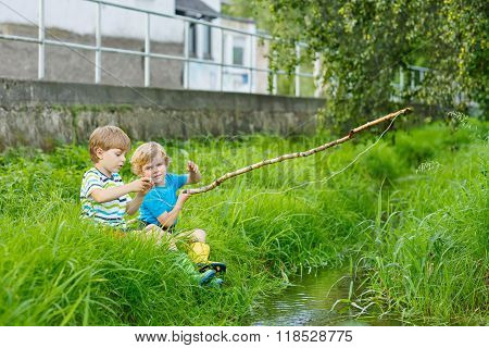 Two funny little brothers fishing on a river with selfmade fishing rod on sunny summer day. Happy children having fun. Active leisure for children outdoors.