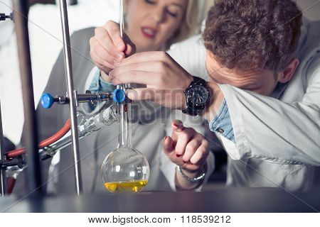 Laboratory equipment for distillation.Student/intern/technician's hands showing experiment.Working in teams for a better result.Science project team work.Making the apparatus in pairs.Work assistance poster