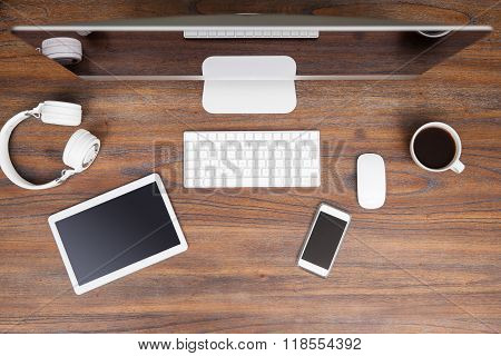 Flay lay of a desktop computer headphones a cup of coffee a tablet and a smartphone on a wooden workspace poster