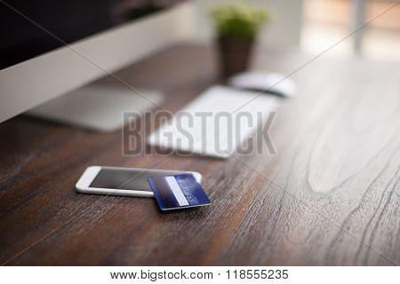 Credit card sitting on a smartphone next to a desktop computer on a modern workspace with shallow depth of field poster