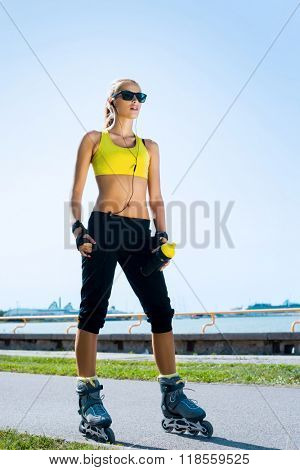 Young, beautiful, sporty and fit girl rollerblading on inline skates poster