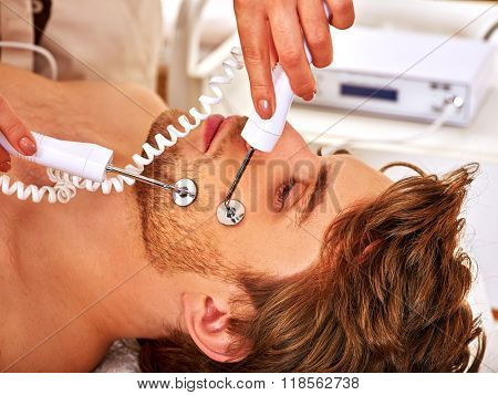 poster of Portrait of handsome man receiving electric facial  therapy hydradermie at beauty salon.