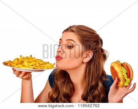Girl eat fastfood big hamburger and fried potatoes .