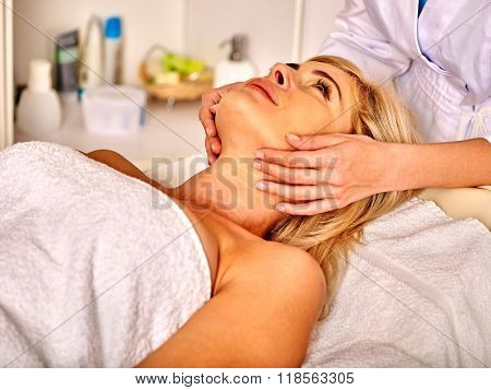 Woman looking up middle-aged take face and neck massage in spa salon.