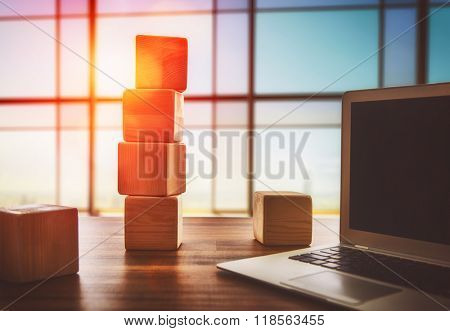The concept of planning in business. Wooden cubes and computer on a desk in the office.