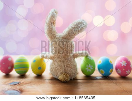 easter, holidays, tradition and object concept - close up of colored easter eggs and bunny over pink holidays lights background
