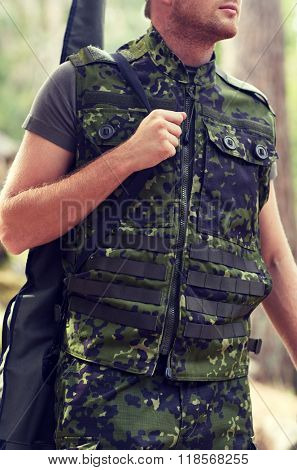 hunting, war, army and people concept - close up of young soldier, ranger or hunter with gun walking in forest