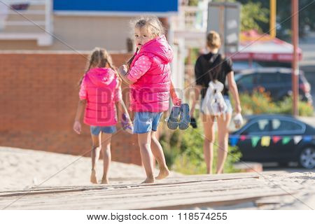 Mother And Two Daughters Are On The Wooden Flooring In The Sand, One Girl Turned