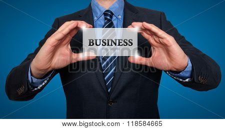 Businessman Holds White Card With Business Sign, Blue - Stock Photo