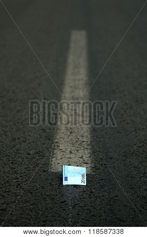 Picture of an Euro money in the middle of the road. Finance concept