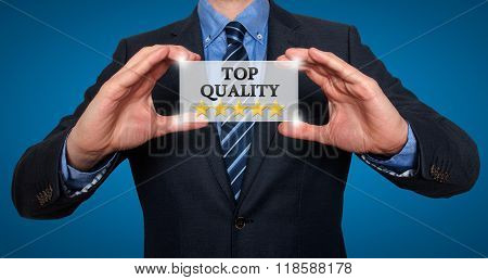 Top Quality With Five Stars - Businessman With Sign - Blue - Stock Photo
