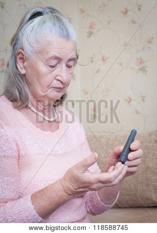 Elderly woman makes testing high blood sugar.