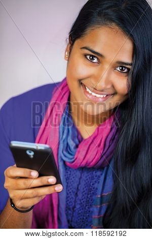 Young beautiful india woman with smart-phone , big smile with long hair and teeth