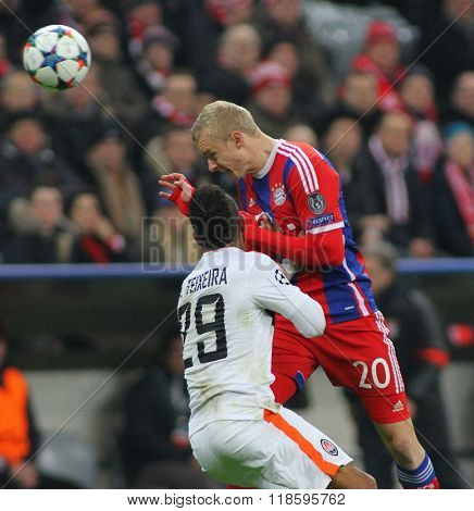 MUNICH, GERMANY - MARCH 11 2015: Shaktar's midfielder Alex Teixeira and Bayern Munich's midfielder Sebastian Rode compete for the ball during the UEFA Champions League match
