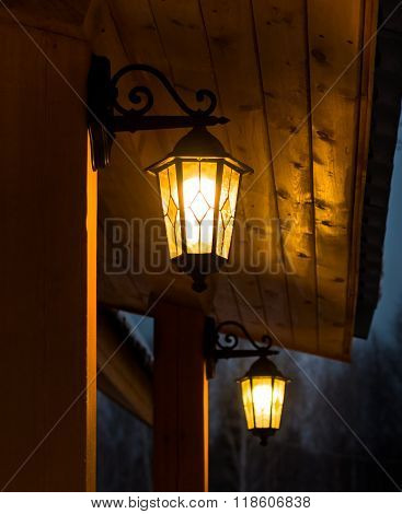 Black Lights With Decorative Glass In Front Of The House Are Lit At Dusk. Focus On Near-lantern