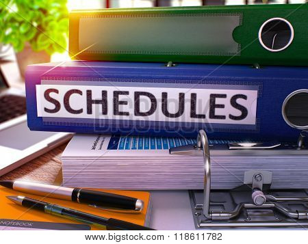 Blue Office Folder with Inscription Schedules on Office Desktop with Office Supplies and Modern Laptop. Schedules Business Concept on Blurred Background. Schedules - Toned Image. 3D. poster