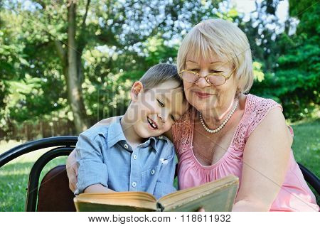 Smiling Boy And His Grandmother Sitting In The Park And Reading A Book