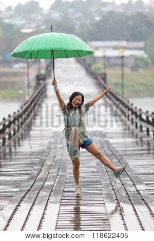 Woman dancing in the rain falling on the Mon wooden bridge of Sangklaburi, Thailand