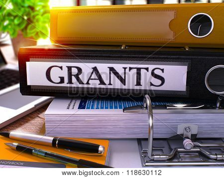 Grants on Black Ring Binder. Blurred, Toned Image.