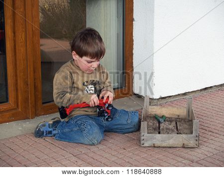 Boy repairing his toy-car