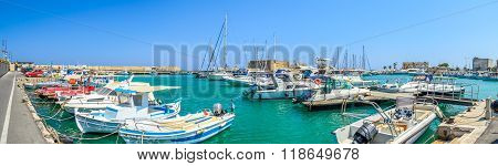 HERAKLION, CRETE, GREECE - AUGUST 11, 2013: Traditional Greek fishing boats and yachts parked in Heraklion harbour. Old Heraklion fortress on background is very popular place on Crete island