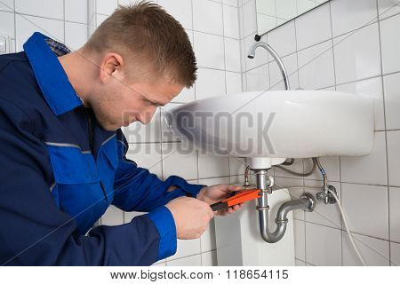 Young Male Plumber Fixing Sink In Bathroom poster