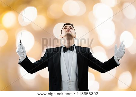 Young male music conductor looking up while holding baton against illuminated background poster
