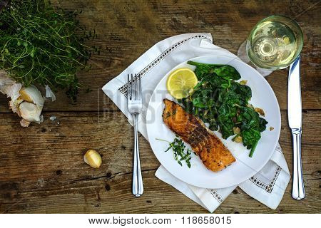 Grilled Salmon With Thyme, Lemon, Spinach And White Wine On A Dark Rustic Wooden Table, Top View Fro