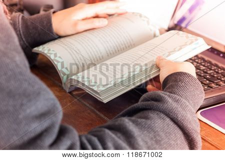 Woman Reading Book On Work Station