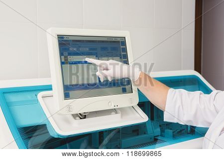 Lab tech loading samples into a chemistry analyzer