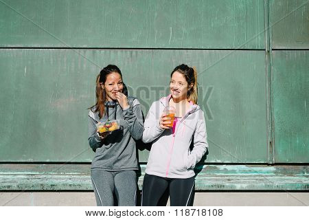 Sporty women eating healthy food after outdoor fitness workout. Fitness diet nutrition with fruit salad and carrot orange detox smoothie.
