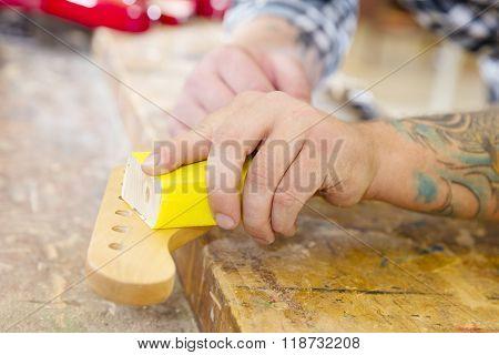 Carpenter sanding a guitar neck in wood at workshop