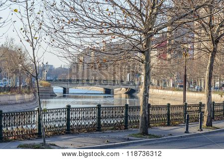 Bucharest Romania - January 10: Dambovita River on January 10 2016 in Bucharest. Winter cityscape with frozen tree buildings river and bridge. poster