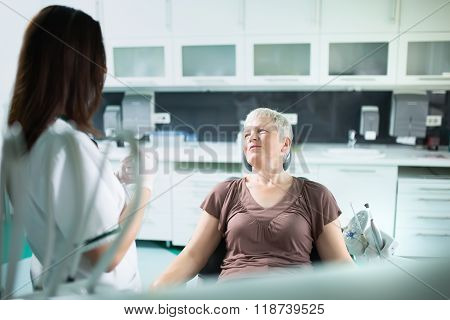 Old woman visiting the dentist taking care of her teeth.Dentist doctor talking to a senior woman