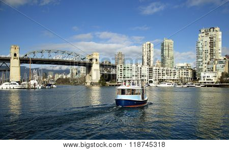Ferry crossing Granville island to downtown with Burrard bridge in background in Vancouver island
