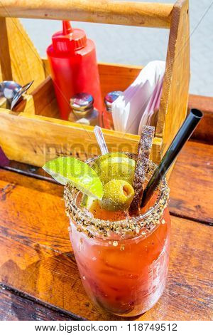 Caesar or bloody mary cocktail drink rimmed with spice and garnished with lime wedge pepper and olives on a hot summer day. poster