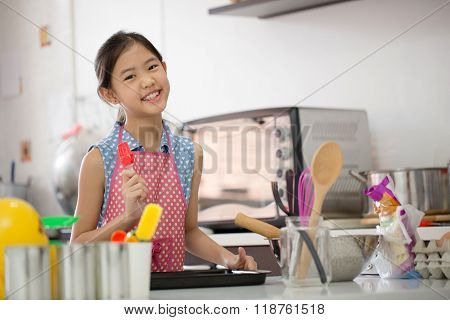 Little Asian cute chef cooking a bakery