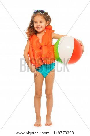 Little swimmer in orange lifejacket and sunglasses standing full length with colored wind-ball