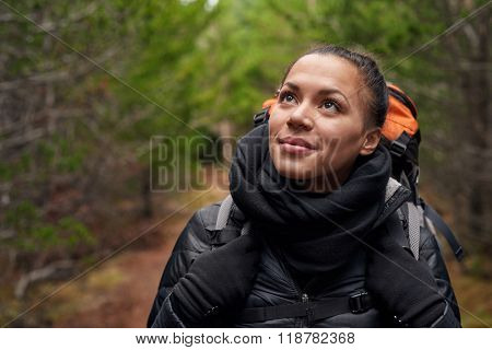 Portrait of a beautiful hispanic woman hiking in the pine forest alone, a solo expedition camping trip