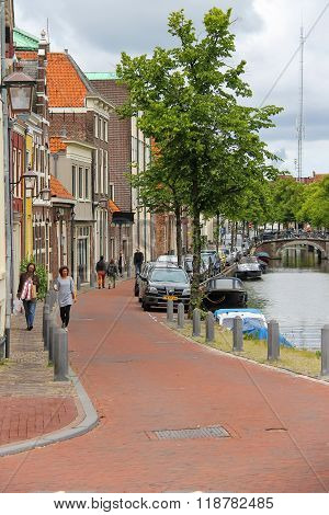 People Walking Along The River Channel In The Historic Centre Of Haarlem, The Netherlands