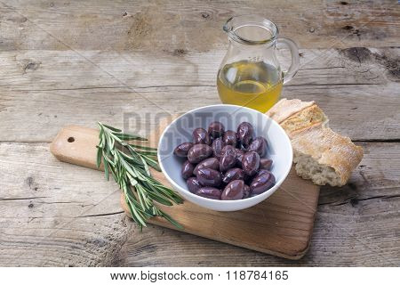 Kalamata Black Olives, Oil, Bread And Rosemary Garnish On Rustic Wood