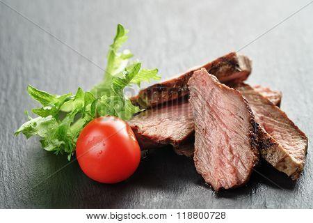entrecote beef steak sliced on slate board with vegetables