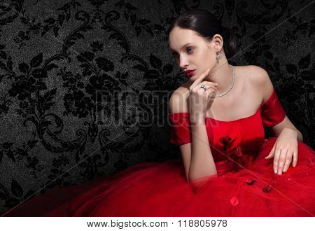 Beautiful woman in red evening dress on dark background. Space for text.