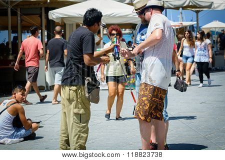 Selfie stick seller sells sticks to tourist at street of Chania town on Crete island, Greece