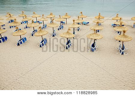 Group of umbrellas and sunloungers on empty beach.