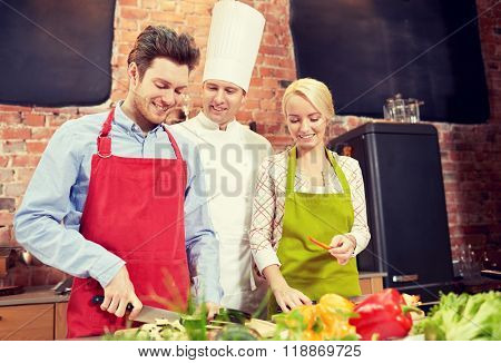 cooking class, culinary, food and people concept - happy couple and male chef cook cooking in kitchen