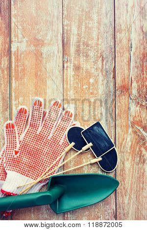 gardening and planting concept - close up of trowel, nameplates and garden gloves on table