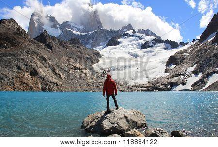 Man, blue lake, glacier and mountains.