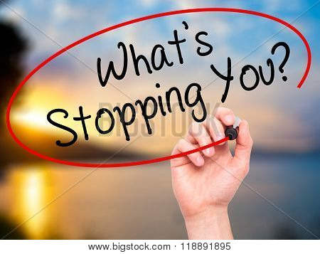 Man Hand Writing What's Stopping You?  With Black Marker On Visual Screen